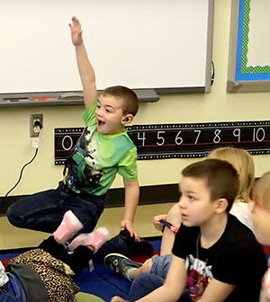 Boy energetically raising his hand in class